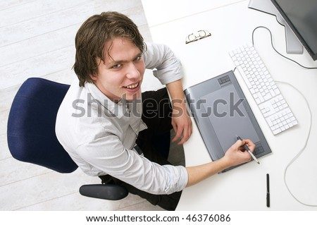 Portrait of a man sitting behin a desk with keyboard, graphic tablet and monitor in an office