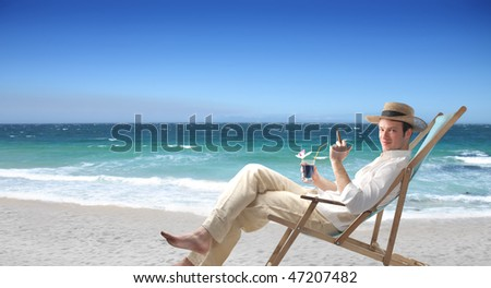 Portrait of a man sitting on a deckchair on a beach and holding a glass of wine and a cuban cigar