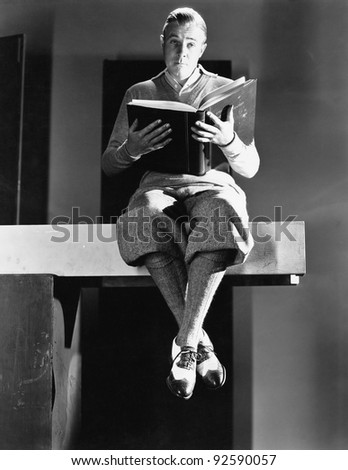 Portrait of a man sitting on a wooden plank and holding a book