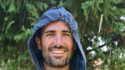 Portrait of a man smiling happy in the rain and breathing air of freedom, dreams, and love for nature. Concept of: lifestyle, nature, freedom, rain and happiness