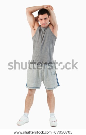 Portrait of a man stretching his arm against a white background