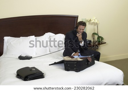 Portrait of a man talking on the phone as he unpacks a suitcase in his hotel room