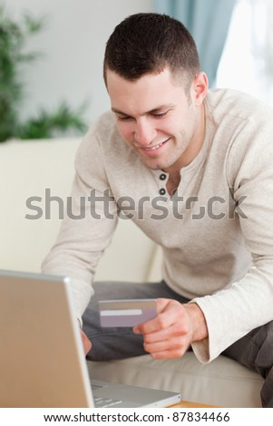 Portrait of a man using a laptop to book a flight in his living room