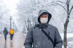 Portrait of a man wearing a medical protective mask on his face in winter, Covid-19 coronavirus pandemic, virus protection.