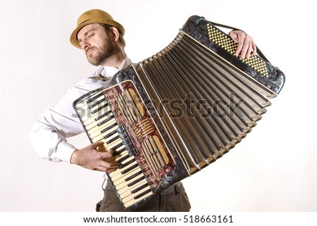 Portrait of a man wearing a straw hat and a white shirt emotionally playing the accordion