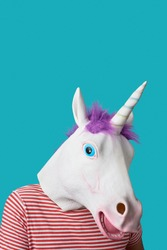 portrait of a man wearing a unicorn mask and a red and white striped t-shirt, on a blue background with some blank space on top