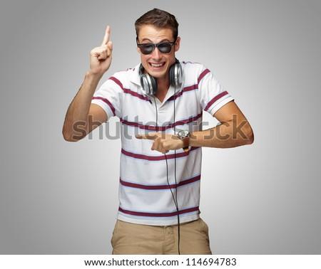 Portrait Of A Man Wearing Headphone Dancing On Grey Background
