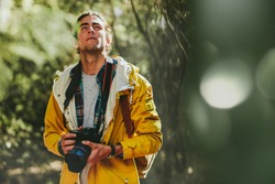 Portrait of a man wearing jacket and backpack walking in a forest holding a dslr camera. Man exploring a forest capturing the beauty in a digital camera.