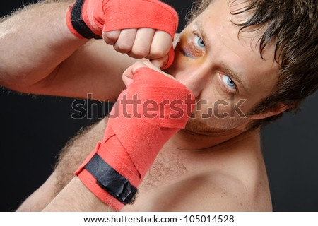 Portrait of a man with a bruise in a battle position. Clenched fists. Dark background.