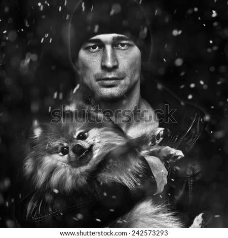 Portrait of a man with a dog on a black background, the snow falls
