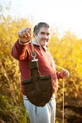 Portrait of a man with a search magnet. His hobby is magnetic fishing.