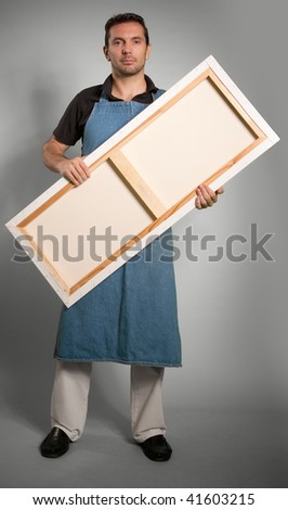 Portrait of a man with an apron holding a canvas