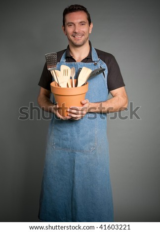 Portrait of a man with an apron holding a pot with cooking tools