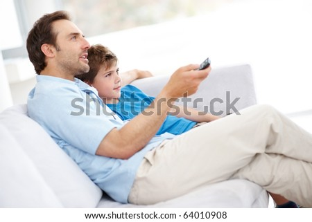 Portrait of a man with remote control and his son sitting together watching television at home Indoor