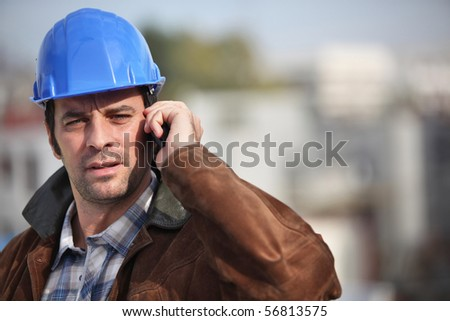 Portrait of a man with safety helmet and a mobile phone