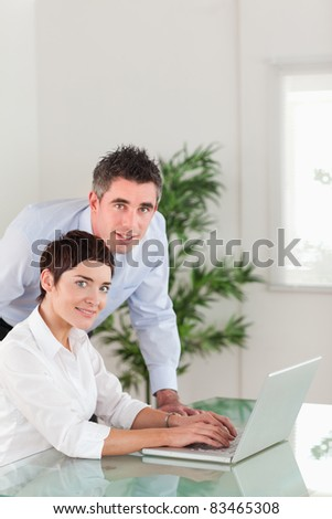 Portrait of a manager and his secretary posing with a laptop in an office