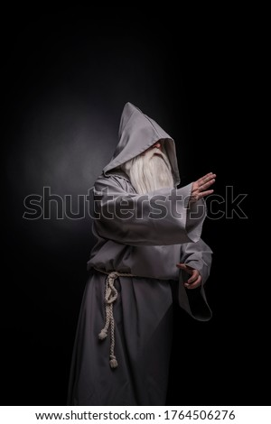 Portrait of a manly and brutal, majestic, old man, sorcerer, wizard with gray hair and a beard with a mustache, in gray clothes, a canopy and tunic on a gray background Сток-фото ©