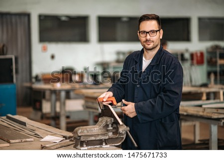 Portrait of a manual worker in metallurgical plant workshop.