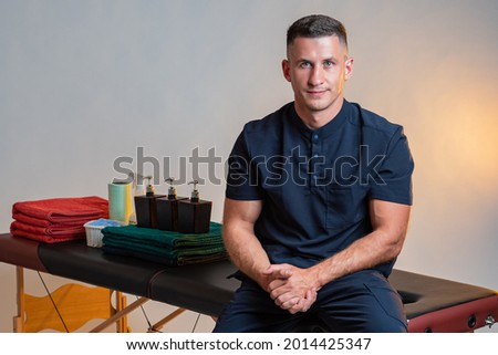 Portrait of a masseur. Masseur grooves into couches. Massage couch is behind him. Massage supplies in background. Masseur looks into camera. Concept of work in spa area. Portrait manual therapist. Stockfoto ©
