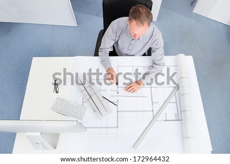 Portrait Of A Mature Architect Drawing Plan On Blueprint In Office
