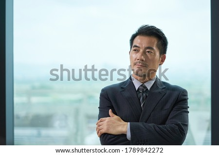 portrait of a mature asian business man standing by window in office arms crossed
