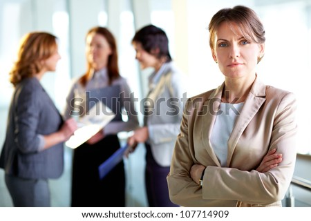 Portrait of a mature business lady standing in the foreground, her female colleagues having a talk in the background