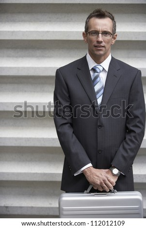 Portrait of a mature businessman holding briefcase