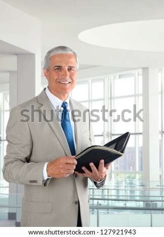 Portrait of a mature businessman standing in a modern office. Man is holding a small binder and smiling at the camera.