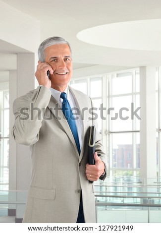 Portrait of a mature businessman standing in a modern office talking on a cell phone.. Man is holding a small binder and smiling at the camera.