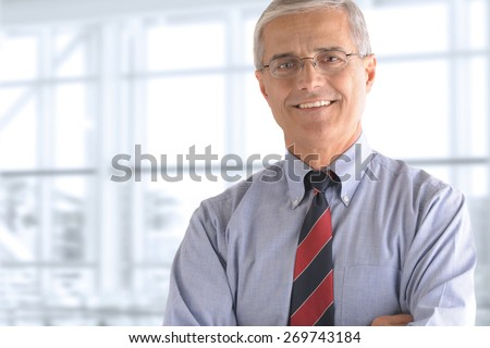 Portrait of a mature businessman standing in front of a large office window. The man is smiling and has his arms crossed.