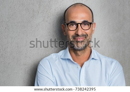 Portrait of a mature businessman wearing glasses on grey background. Happy senior latin man looking at camera isolated over grey wall with copy space. Close up face of happy successful business man. #738242395