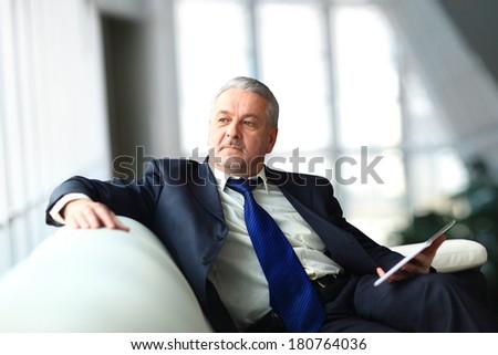 Portrait of a mature businessman with digital tablet