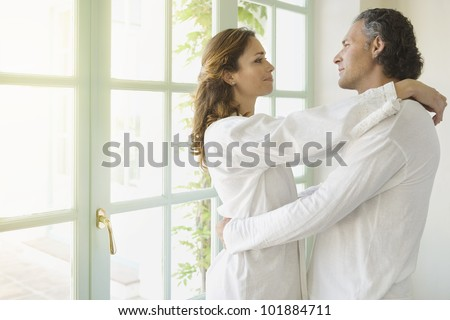 Portrait of a mature couple hugging at home, standing by large garden doors.