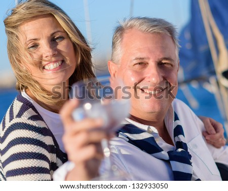 Portrait Of A Mature Couple Offering A Glass Of Wine