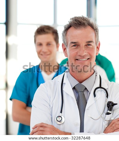 Portrait of a mature doctor leading his team in hospital