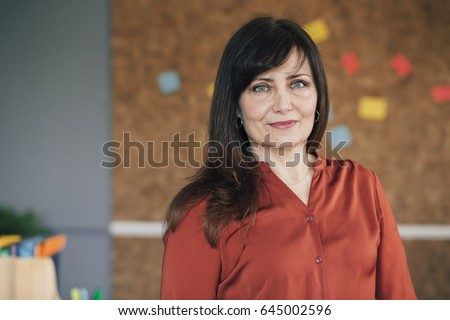 Portrait of a mature, female business owner in her office. She is standing in front of a cork board and is smartly dressed, smiling for the camera.