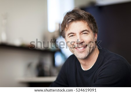 Portrait Of A Mature Handsome Man Smiling At The Camera. Home