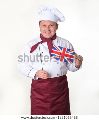 Portrait of a mature male cook with Great Britain flag standing on a light background.