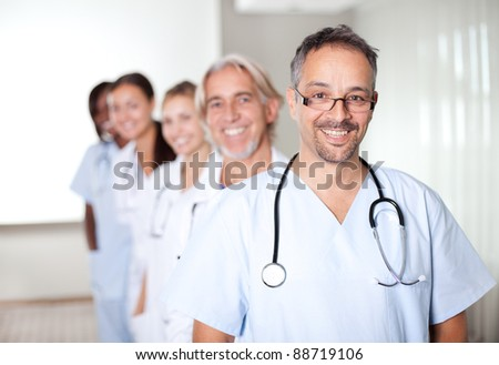 Portrait of a mature male doctor standing in front of his team and smiling - stock photo