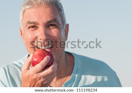 Portrait of a mature man about to eat a red apple