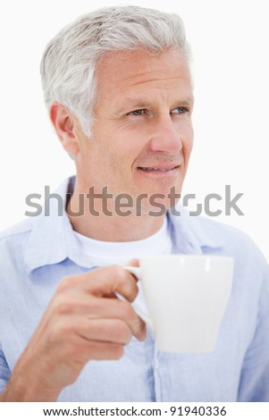 Portrait of a mature man drinking tea against a white background
