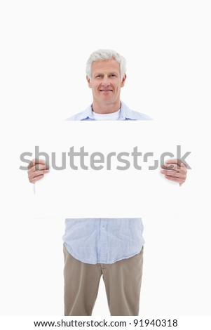 Portrait of a mature man holding a blank panel against a white background