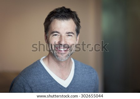 Portrait of a mature man smiling at the camera #302655044