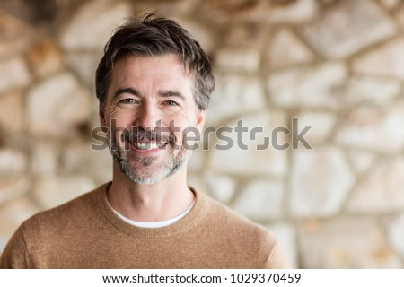 Portrait Of A Mature Man Smiling At The Camera. Home #1029370459