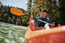 Portrait of a mature man with kayak in a lake. Caucasian man paddling a kayak on summer day.