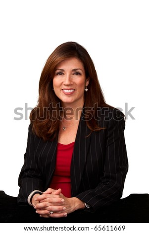 Portrait of a mature pretty businesswoman wearing red blouse and a black jacket and sitting a small black table.  Isolated on white background.