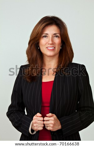 Portrait of a mature pretty businesswoman wearing red blouse and a black jacket. Isolated on white background. Arms are folded.