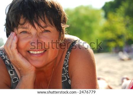 Portrait of a mature woman lying on a sandy beach