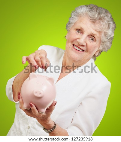 Portrait Of A Mature Woman With A Piggy Bank On Green Background