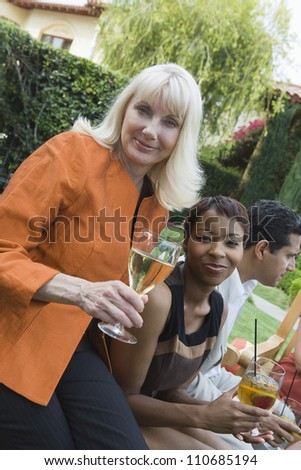 Portrait of a mature woman with friends celebrating with wine